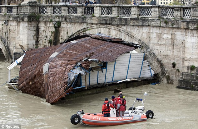 Rescuers look at a houseboat stuck in the arch of Sant'Angelo bridge on the Tiber river in downtown Rome today