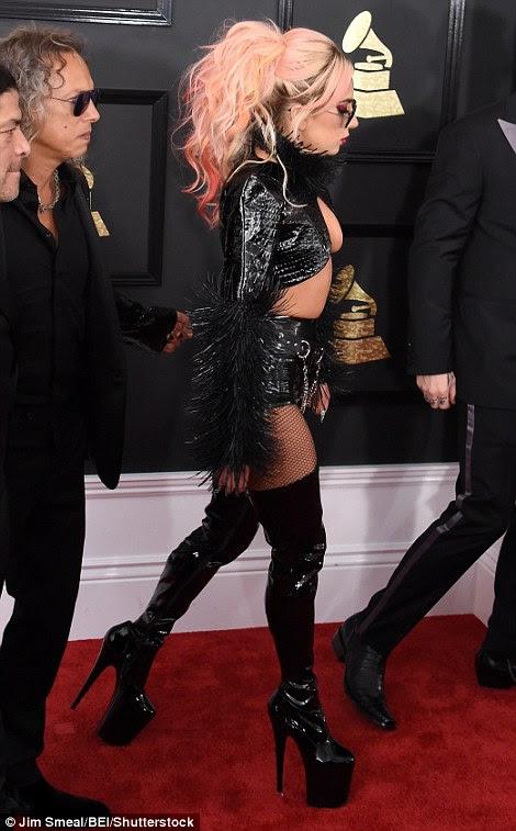 Suportando suas coisas: Gaga usava extensões coloridas rosa empilhadas em um rabo de cavalo e um par de botas de plataforma