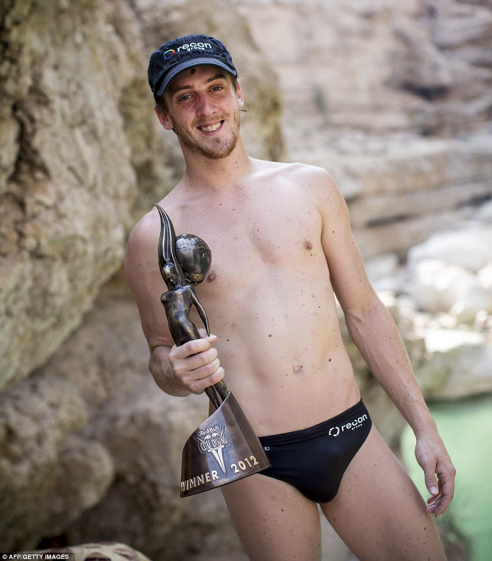 Nerves of steel: Gary Hunt of Great Britain clutches the World Series trophy after the seventh and final stop of the Red Bull Cliff Diving World Series at Wadi Shab in Oman