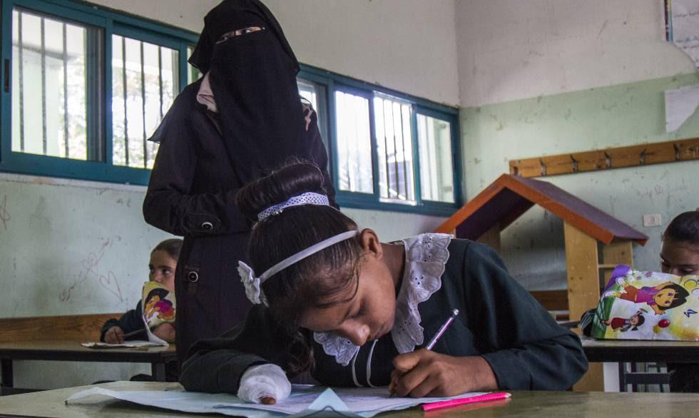 Doaa, con la mano vendada, hace los deberes en el colegio.