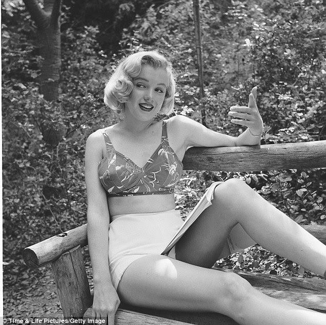 Em ação: Enquanto estava sentado num banco de madeira, Marilyn tem um script aberto no colo e mima uma cena