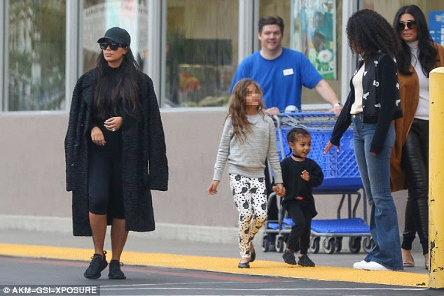 Oh goodie: North was practically skipping with glee as she emerged from the store beside a toy-laden cart