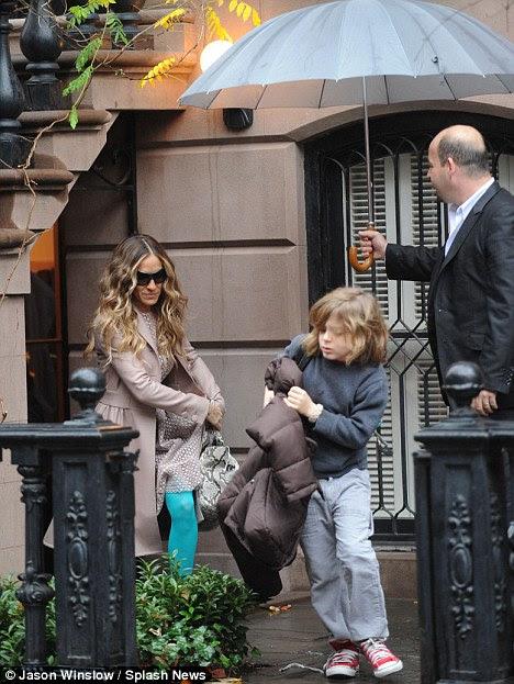 Mãe em fuga: Jessica foi flagrada levando seu filho James para a escola na chuvosa Big Apple