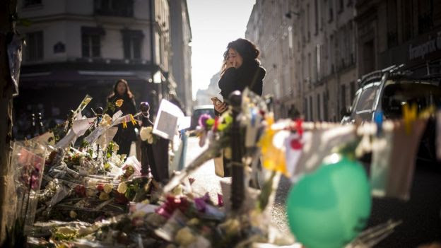 A person cries as she stands at a makeshift memorial for a tribute to the victims of a series of deadly attacks in Paris, in front of the Casa Nostra restaurant in Paris on November 23, 2015