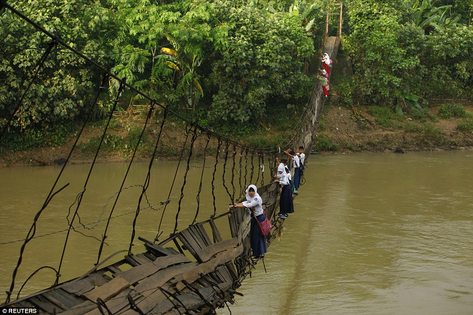 Determined: Students in Indonesia cling to steel bars on a broken bridge as they cross Ciherang River near their village in Lebak Regency. A pillar supporting one side of the crossing collapsed, leaving the wooden planks that acted as a path tilted to one side
