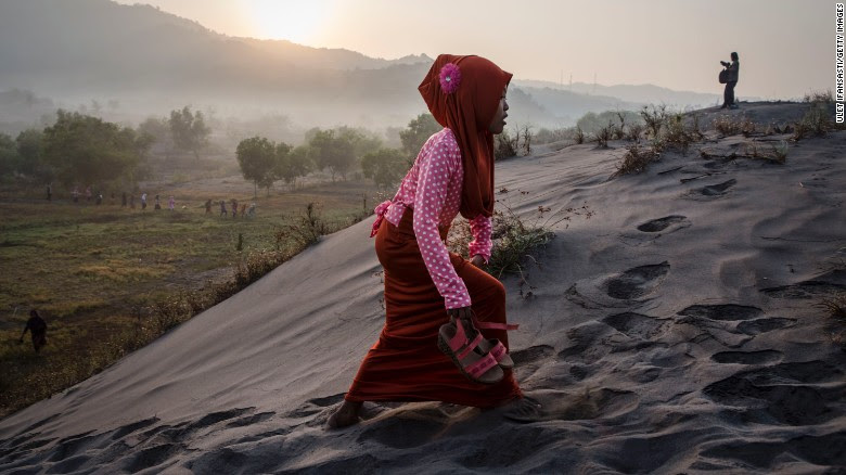 A Muslim woman walks on 'sea of sands' as they prepare for  prayer at Parangkusumo beach  in Yogyakarta, Indonesia.