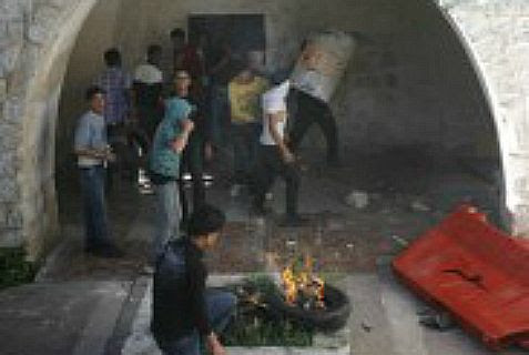 Masked Palestinian youth burn tires and throw stones in Joseph's Tomb. (archives)