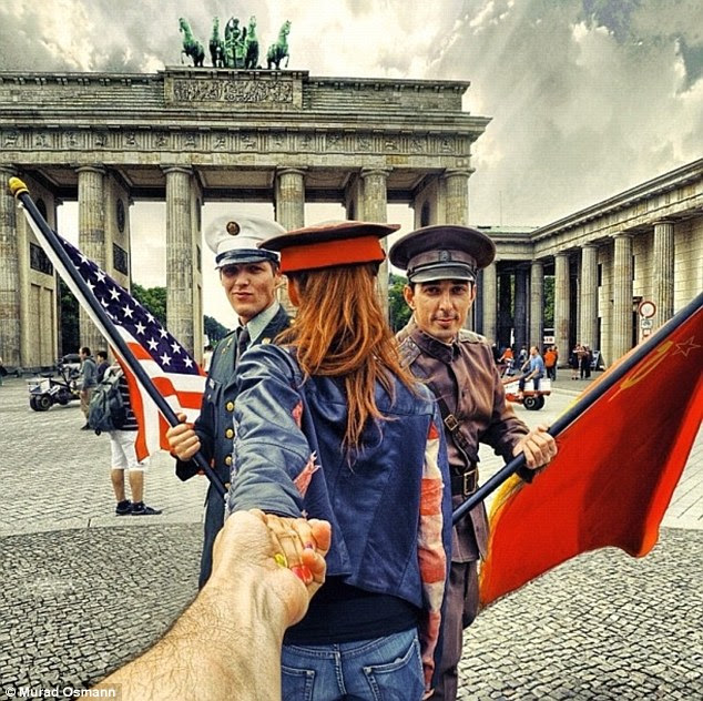 Cultural exchange: The pair pose with actors dressed as cold war soldiers outside the Brandenburg Gate in Berlin, Germany