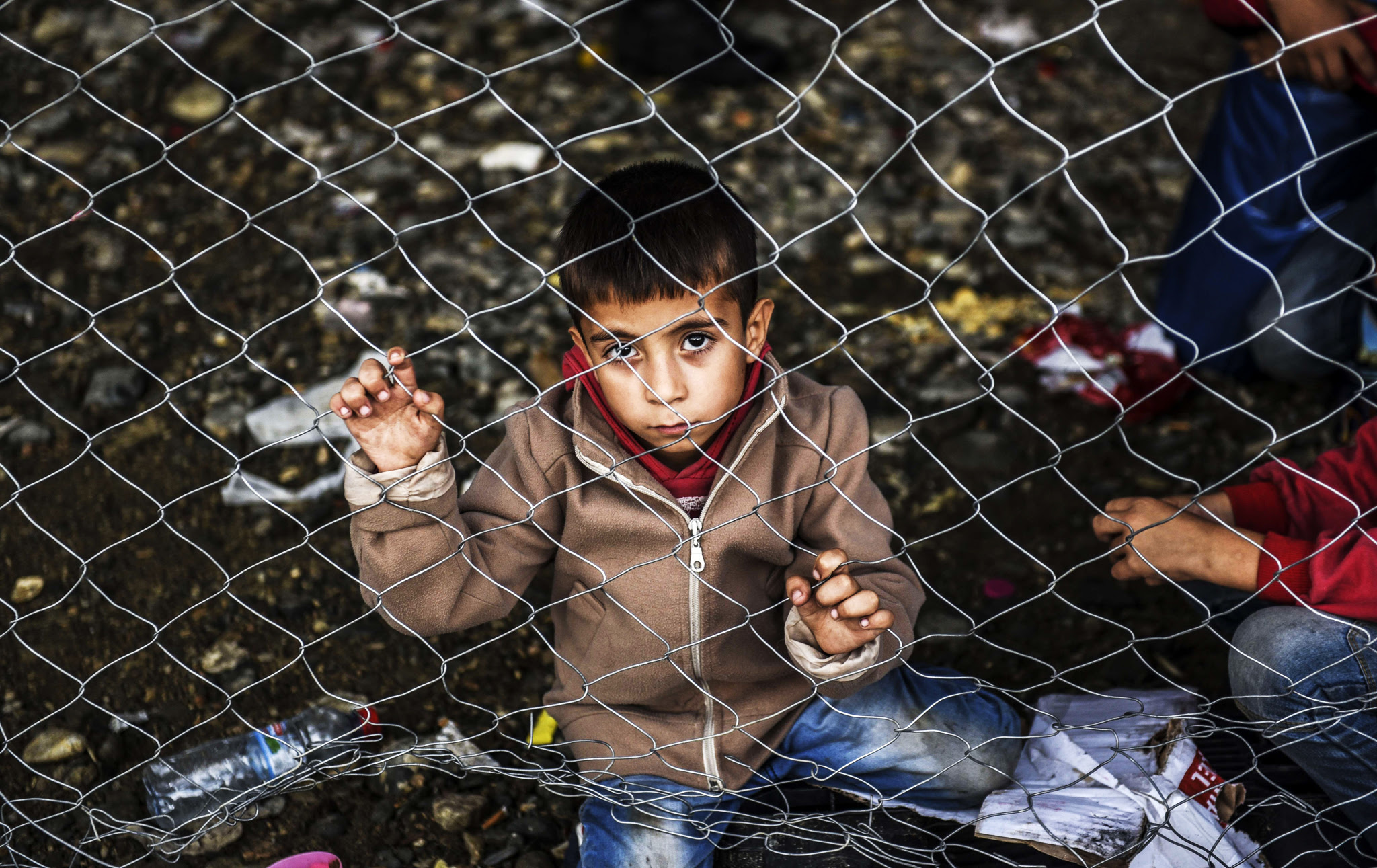 A child sits behind a fence as refugees and migrants wait for a train heading to Serbia near the Macedonian-Greek border on September 25, 2015. European Union leaders hold an emergency migration summit on September 23 amid a growing east-west split after ministers forced through a controversial deal to relocate 120,000 refugees.