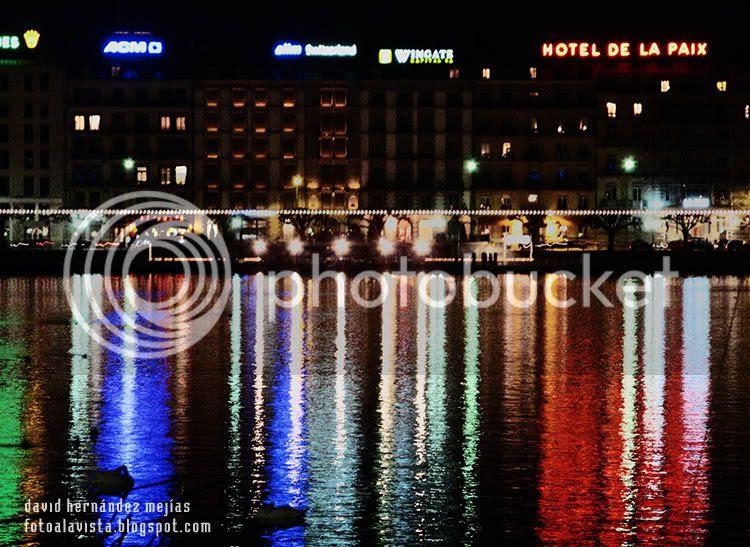Reflejos en la noche de las luces de los edificios y hoteles de Ginebra (Suiza) sobre el lago Lemán