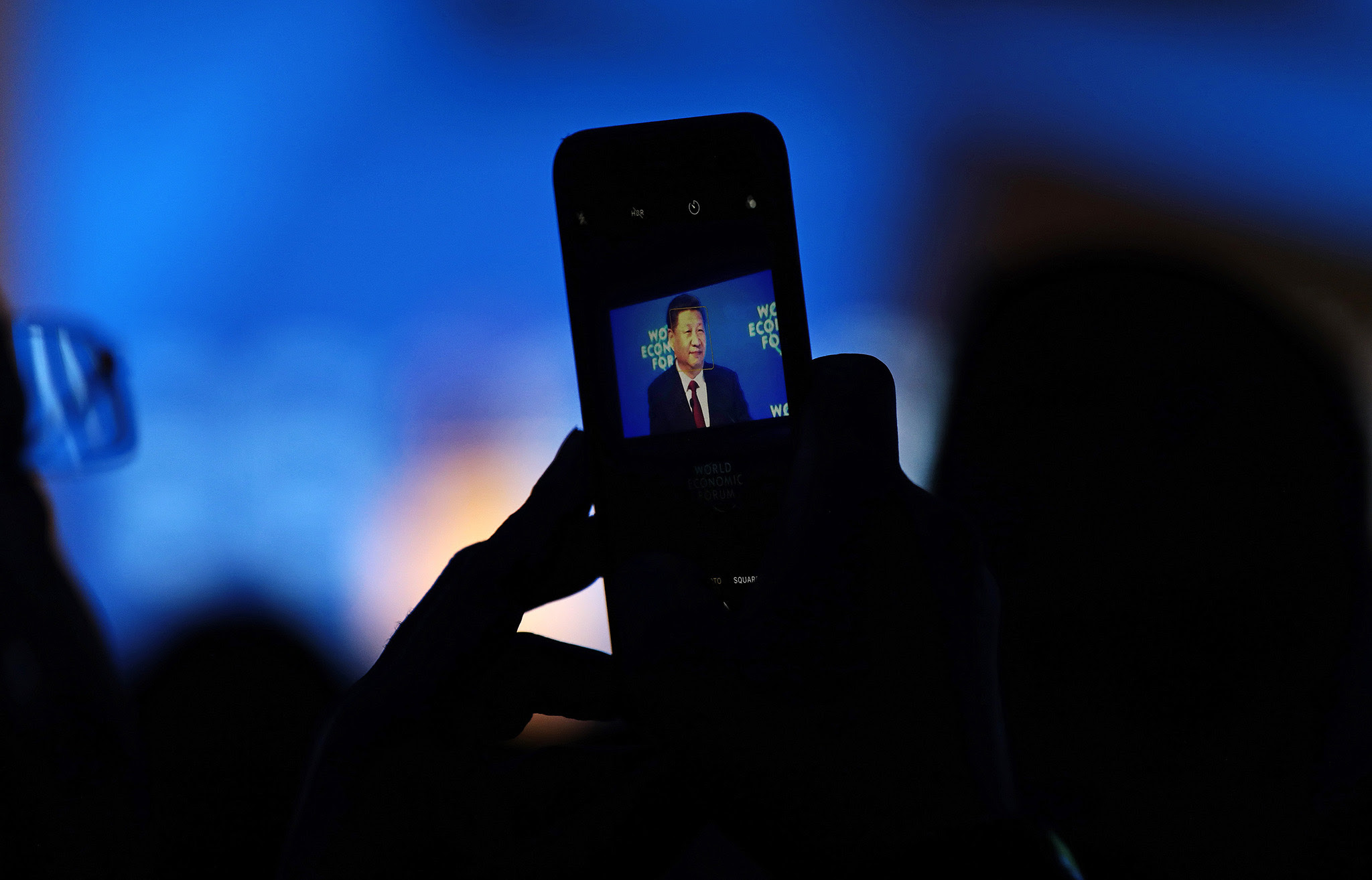 An attendee films Xi Jinping, China's president, on a mobile device as he speaks during the opening plenary session of the World Economic Forum (WEF) annual meeting in Davos, Switzerland, on Tuesday, Jan. 17, 2017. World leaders, influential executives, bankers and policy makers attend the 47th annual meeting of the World Economic Forum (WEF) in Davos from Jan. 17-20. Photographer: Simon Dawson/Bloomberg