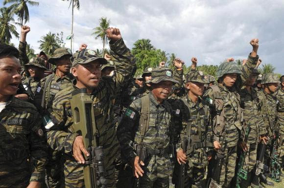 Moro Islamic Liberation Front (MILF) forces raise their fists during a show of force inside the camp in Camp Darapanan, Maguindanao province, southern Philippines March 27, 2014. REUTERS/Stringer