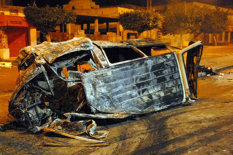A picture taken on Thursday shows a burnt car on a street in Ettadhamen city, west of the Tunisian capital, following a wave of protests and clashes which have brought fresh crisis to the country, five years on from the Arab Spring.