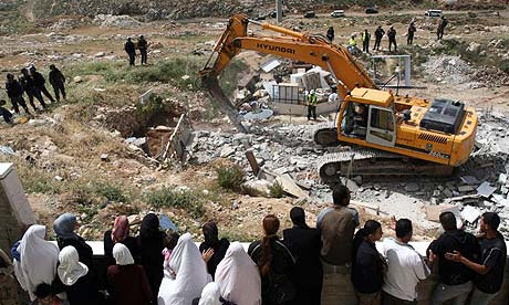 Palestinians watch an Israeli bulldozer destroying a Palestinian house in a village in the West Bank