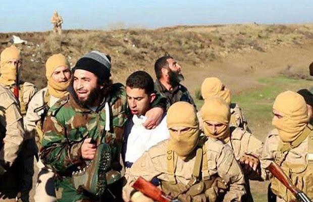 Imagem postada pelo centro de mídia do grupo Estado Islâmico mostra o que seria o piloto capturado (de branco, ao centro), em Raqqa (Foto: AP)
