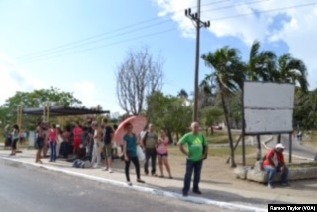 People line up on the sidewalk while waiting for a bus, on the outskirts of Havana.