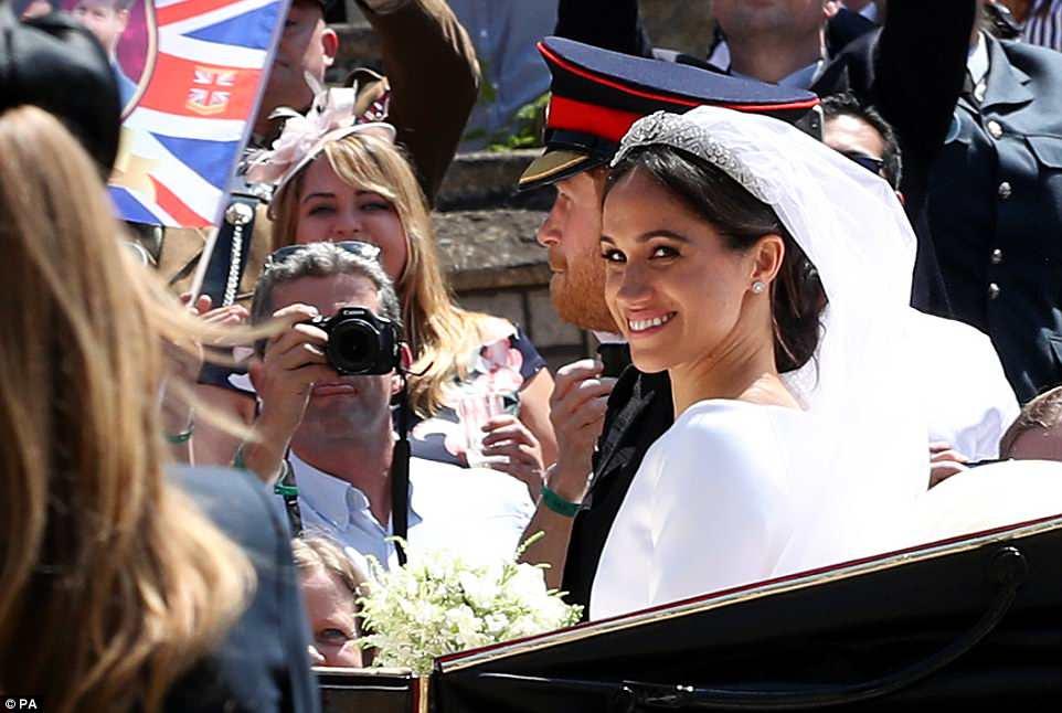 Meghan sonríe mientras los entusiastas de la realeza toman una foto del Duque y la Duquesa de Sussex en Windsor