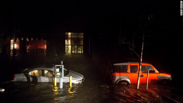 Flooded cars line the streets of New York's financial district Monday night.
