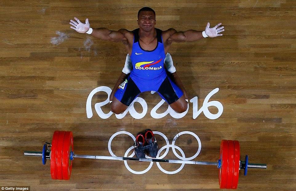 Oscar Albeiro Figueroa Mosquera remove seus sapatos, sinalizando sua aposentadoria do esporte, e olha para o céu depois de tomar a medalha de ouro na weightlifing para a Colômbia