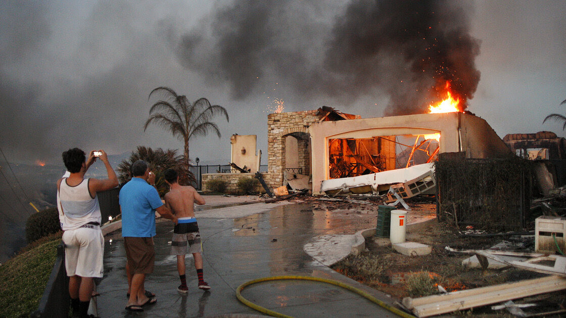 Residents photograph the burning ruins of their home in Carlsbad, Calif., that was destroyed in the Poinsettia fire, one of nine wildfires that have erupted in San Diego County.