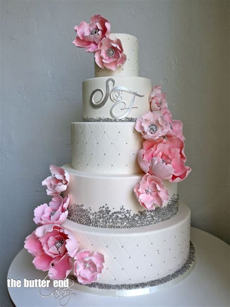 White and silver wedding cake with pink sugar flowers and