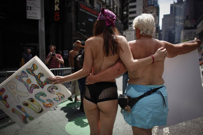 People participate in the GoTopless pride parade in Manhattan on Sunday in New York City.