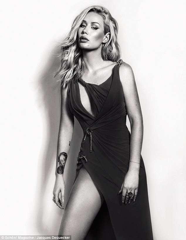 Glam: The singer, who is releasing her second album this year, dresses up in a black dress with a daring split for another racy shot