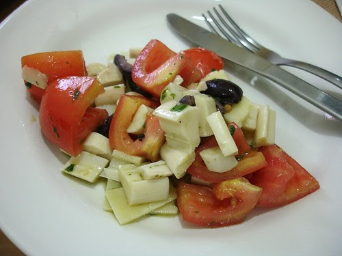 Tomato, hearts of palm, olive and parmesan salad with basil dressing