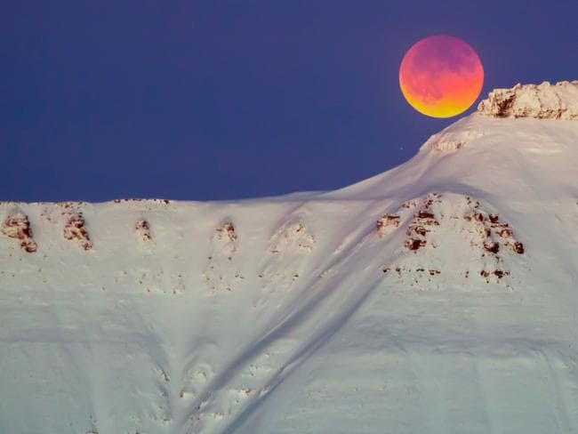A super blue blood moon behind a mountain is seen from Longyearbyen, Svalbard, Norway. Picture: AFP