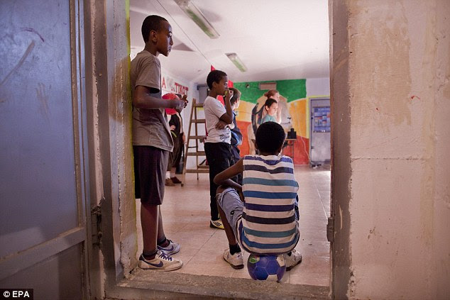 Cover: Ethiopian Israeli kids in the entrance to a bomb shelter in the southern Israeli town of Ashkelon. Lots of people now spend most the day inside, as air raid sirens, signaling missile attacks from the Gaza Strip are so common