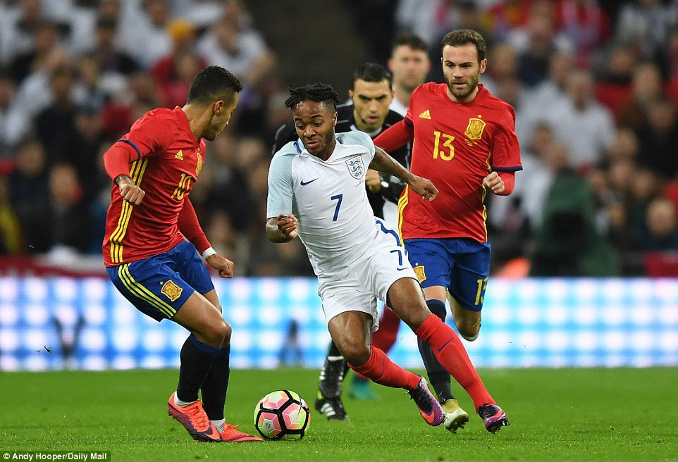 England and Manchester City winger Sterling (centre) takes on Spain and Bayern Munich midfielder Thiago Alcantara (left)