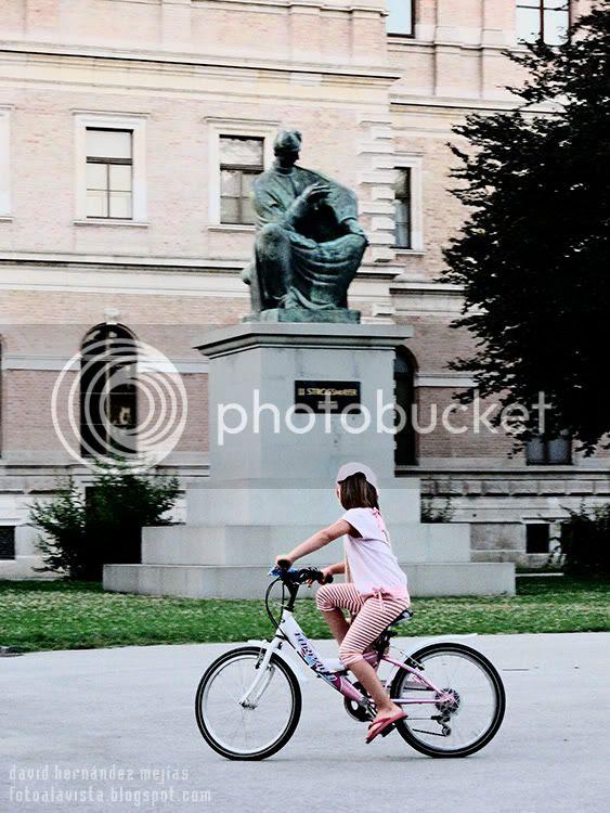 Una niña pasa en bicicleta por delante de una escultura sedente en Zagreb