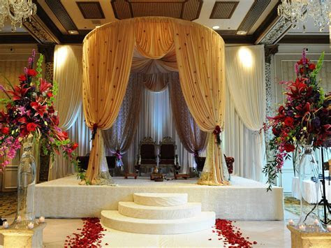 Golden mandap design with light touches of orchids. #