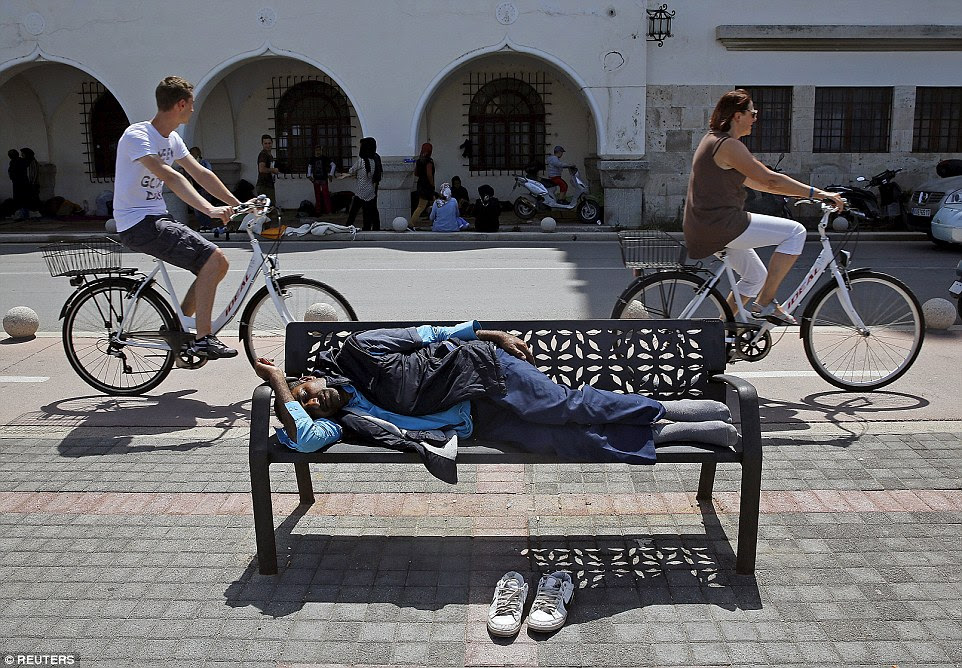 An Afghan immigrant sleeps on a bench outside the police station in Kos as two tourists cycle by. Straggly migrants straight from the boats have been marching through the town with backpacks on to join friends and register for their travel permits at the police station
