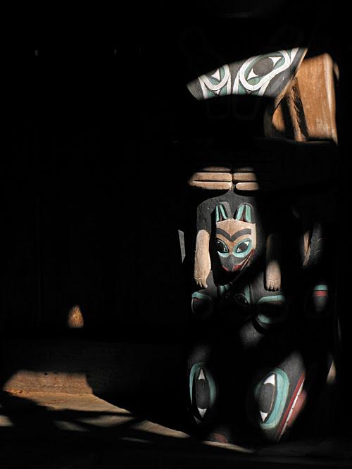 light from the smoke hole dapples a house post, inside Chief Son-i-Hat Whale House, Kasaan, Alaska
