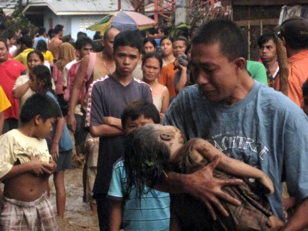An unidentified father cries as he carries the body of his child, who was among hundreds killed by Typhoon Wasi in Cagayan de Oro southern Philippines