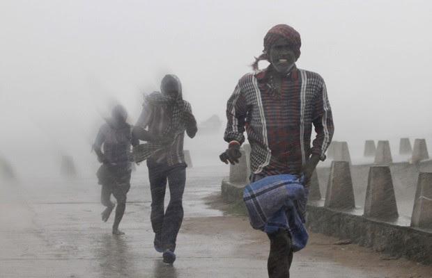 Pessoas correm das fortes chuvas e ventos na região indiana de Gopalpur, em Orissa, neste domingo (12). (Foto: Biswaranjan Rout/AP)
