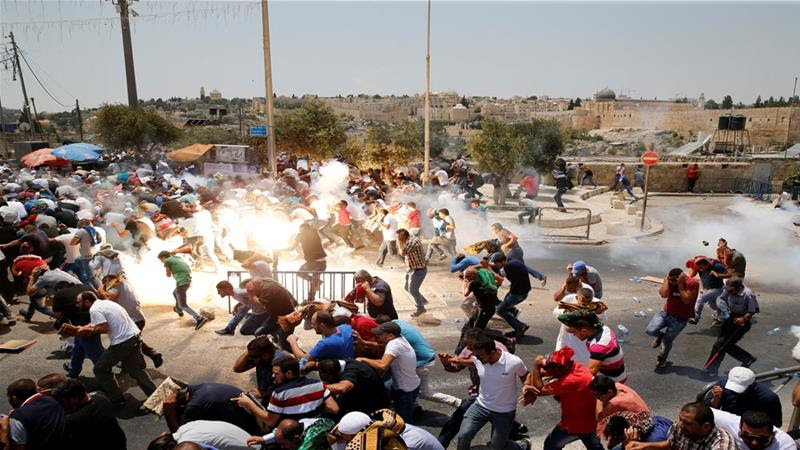 Palestinians react following tear gas that was shot by Israeli forces after Friday prayer on a street outside Jerusalem''s Old city July 21, 2017 [Ammar Awad/Reuters]