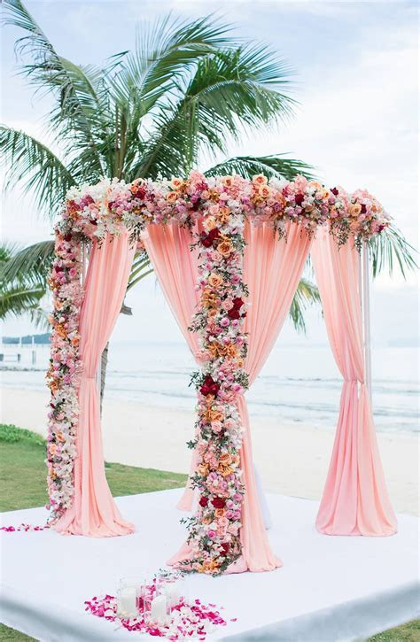 Luxuriously decorated pink arch with blush drapes and