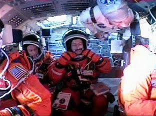 Astronaut Daniel Burbank, center, adjusts his launch and entry suit while sitting in space shuttle Atlantis at the Kennedy Space Center in Florida on September 9, 2006.  Pilot Chris Ferguson, front left, Canadian astronaut Steve MacLean , left, an unidentified NASA worker, top right, and Commander Brent Jett, right , are visible on Atlantis' flightdeck.