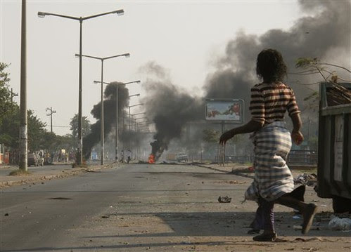 A woman passes nearby burning tires at a street in the capital of Mozambique, Maputo on Sept. 2, 2010. This was the second day of protest over rising food prices in this Southern African nation. by Pan-African News Wire File Photos