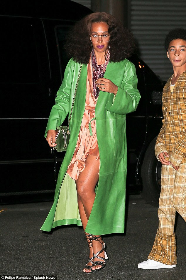 Bold: Solange wore a long, green coat over a peach-coloured dress