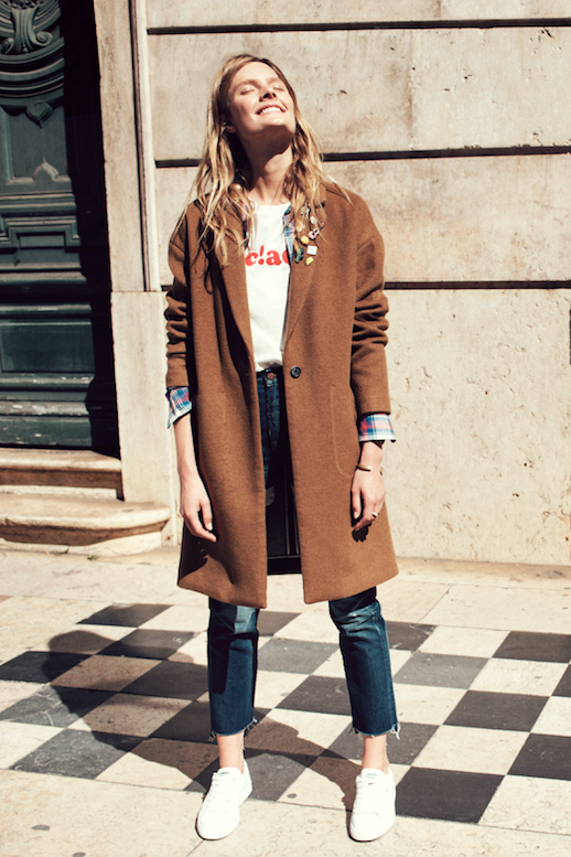 Le Fashion Blog Fall Style Caramel Colored Coat Plaid Shirt Graphic Tee Raw Hem Jeans White Sneakers Via Madewell