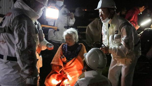 The rescue workers take care of an elderly woman suffering from the shock after the 7.3 magnitude earthquake.