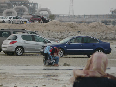 Cars parked on the beach by Al Wakra power station
