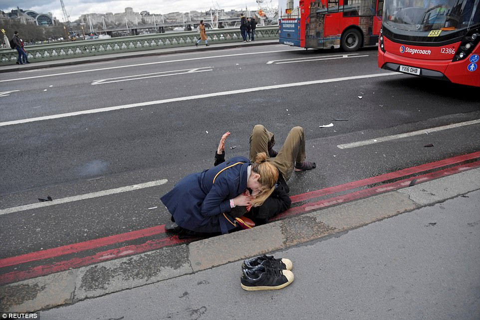 A woman assists an injured person after an incident on Westminster Bridge in London, on March 22, when52-year-old Islamist Khalid Masood, drove a car into pedestrians, injuring more than 50 people, four of whom died. After crashing the car he abandoned it and murdered an unarmed police officer before being shot dead by police