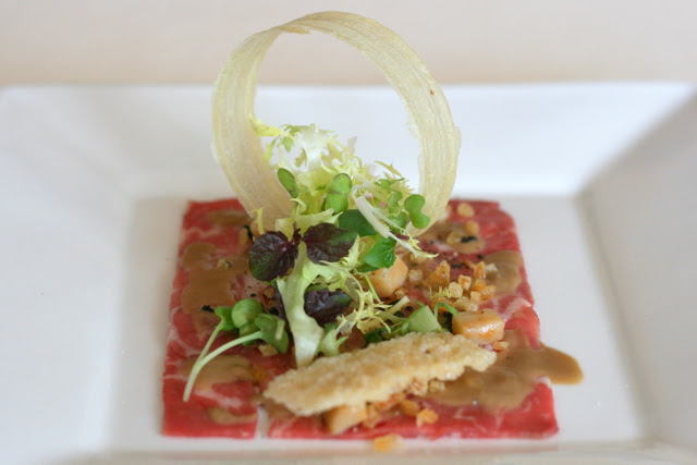 Raw marinated beef tenderloin with truffle vinaigrette and mushrooms