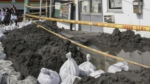 Le 25 mars 2011: Accumulation de boue devant le poste de police d'Urayasu, suite à la liquéfaction des sols. (Masanobu Nakatsukasa/AP/SIPA)