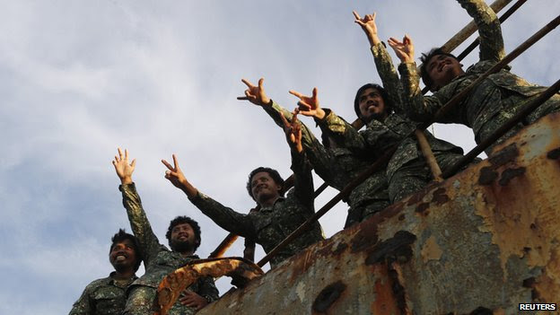 Marines wave at reporters at the disputed Second Thomas Shoal, part of the Spratly Islands, in the South China Sea on 29 March 2014