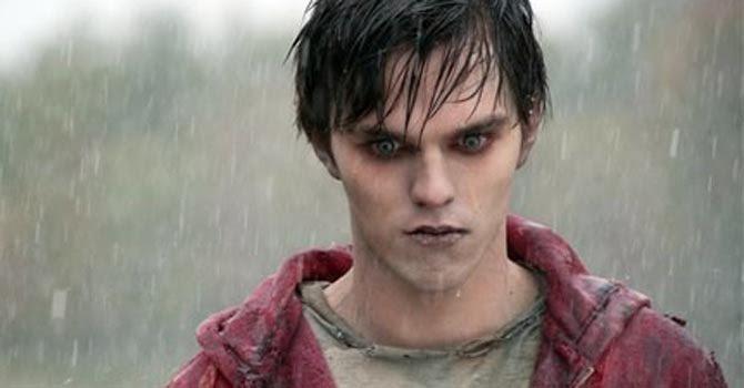 Fotograma de la película Warm bodies, en la que un chico zombie pero con aspecto completamente humano está de pie bajo la lluvia, vistiendo una sudadera roja, piel pálida, pelo negro y ojos azules.